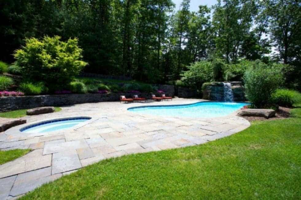 This is the backyard pool area with a large pool that has an attached waterfall and a separate spa-type pool. These are then complemented by the tall trees of the landscaping. Image courtesy of Toptenrealestatedeals.com.