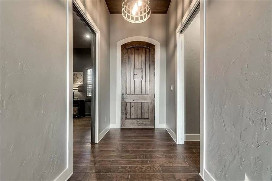 Foyer with an arched entry door and a caged chandelier hanging from the wood-paneled ceiling.