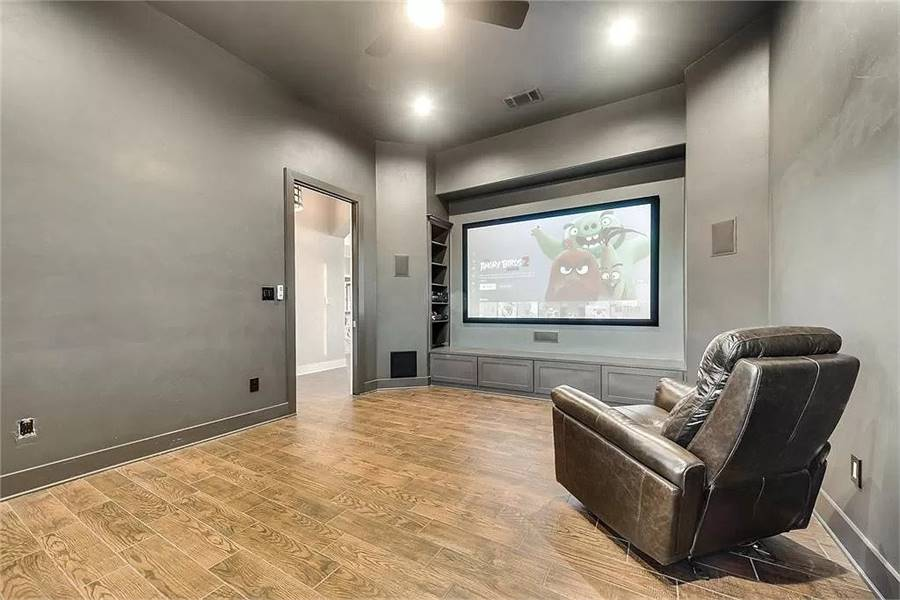 Media room with a leather recliner and a widescreen TV fixed above the built-in base cabinet.