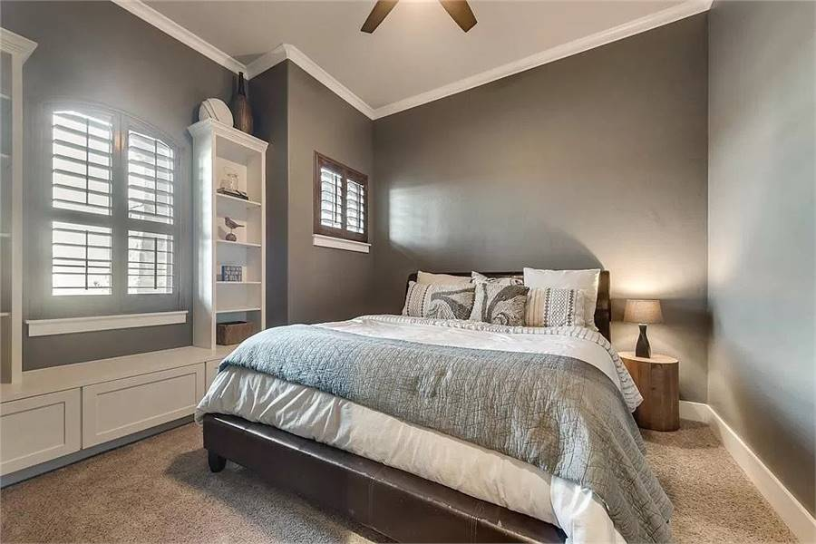 This bedroom has gray walls, carpet flooring, window seat, and a cozy bed.