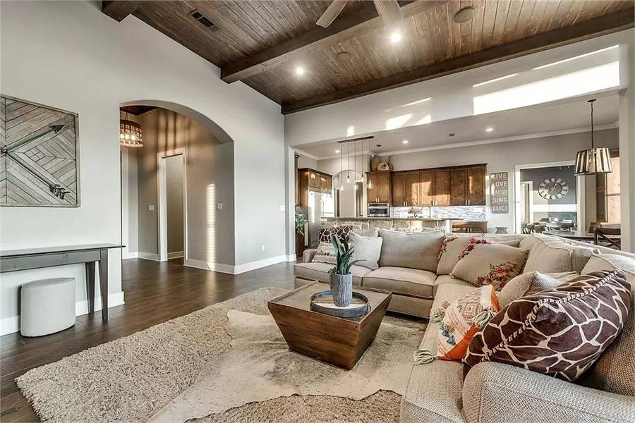 The family room has an L-shaped sectional, a wooden console table, and layered area rugs.
