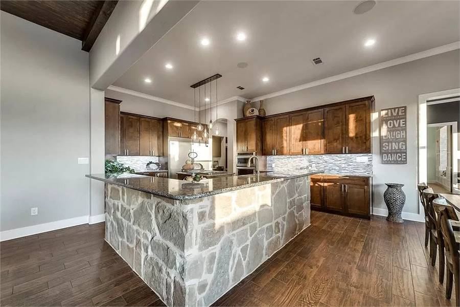 The kitchen is equipped with natural wood cabinets, granite countertops, stainless steel appliances, and a large stone island.