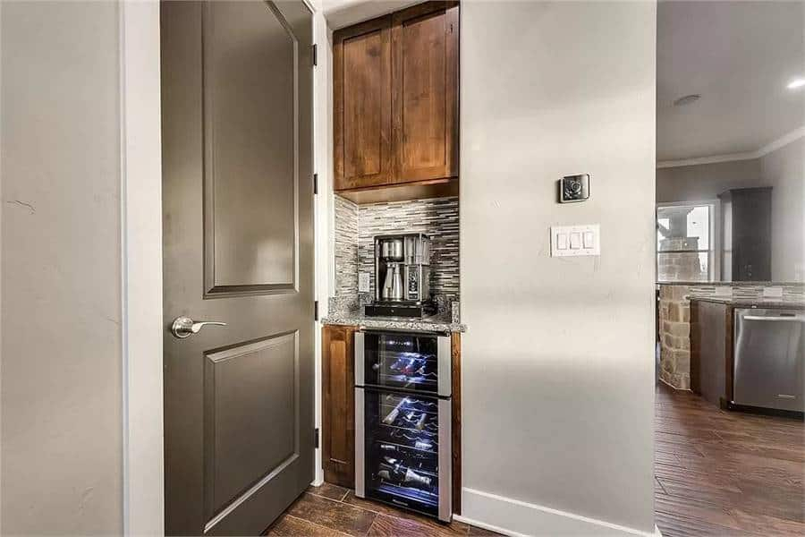 Minibar with wooden cabinets, wine fridge, and a linear mosaic tile backsplash.