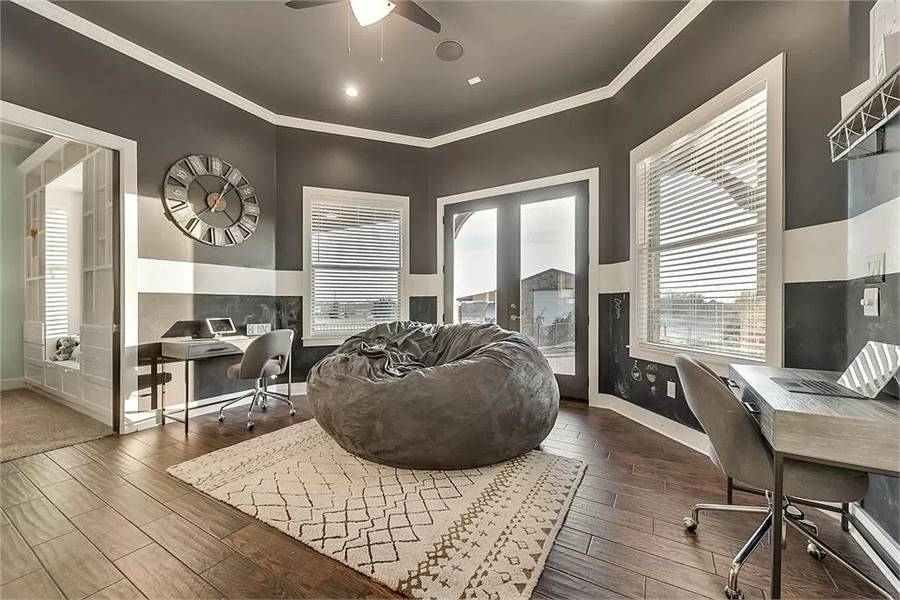 Study with metal desks, swivel chairs, a round wall clock, and a comfy bean bag over a patterned area rug.