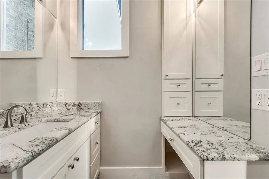 Facing vanities with granite countertops and frameless mirrors.