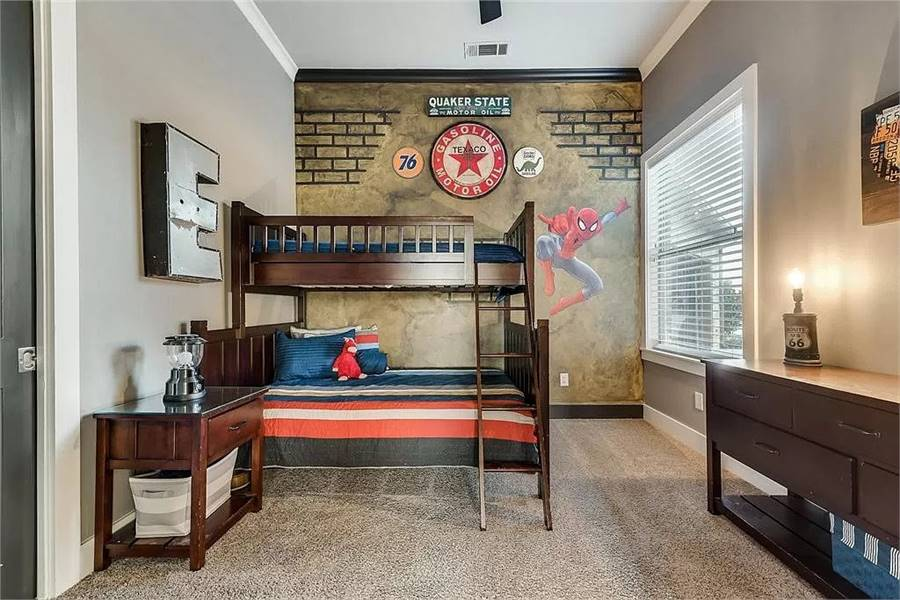 This bedroom has a bunk bed, wooden cabinets, and an accent wall adorned with a spider man mural.