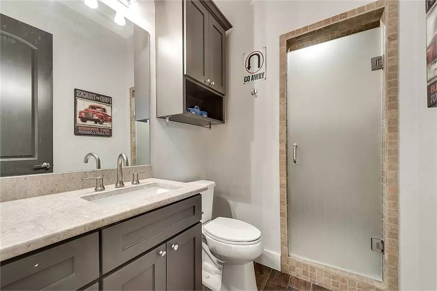 Bathroom with a wooden vanity, a toilet, and a shower area enclosed in a frosted glass door.