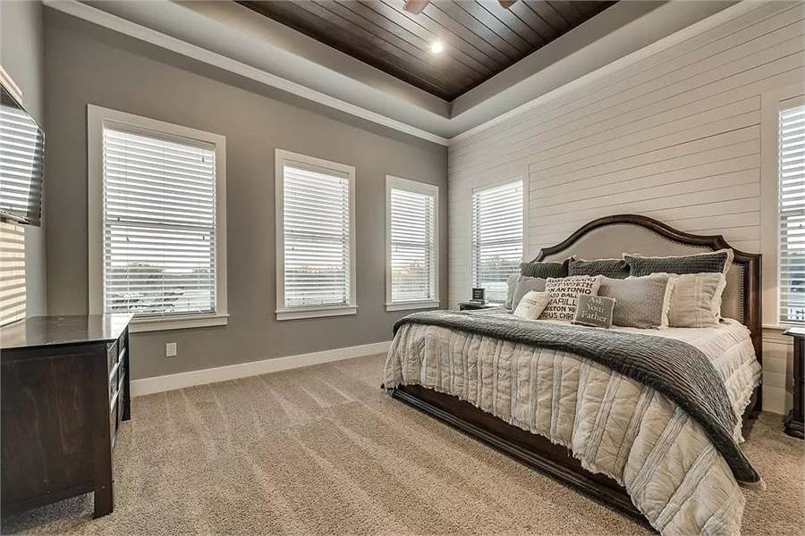 Primary bedroom with dark wood furnishings, carpet flooring, and a tray ceiling clad in wood planks.