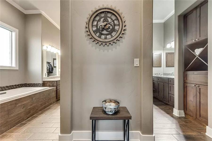A round gear wall clock fixed above the wood top table adorns the primary bathroom.