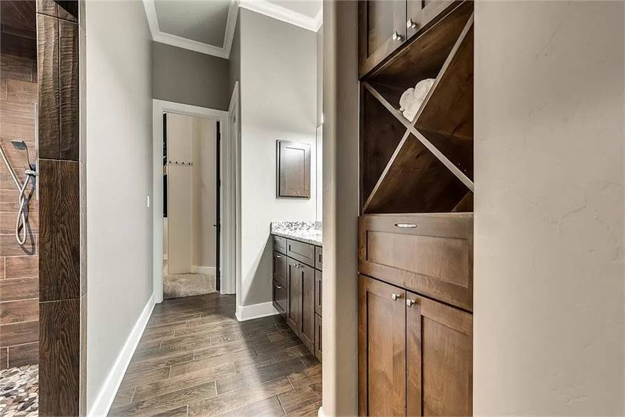 The primary bathroom is equipped with a shower area, wooden cabinets, granite top vanity, and a walk-in closet.