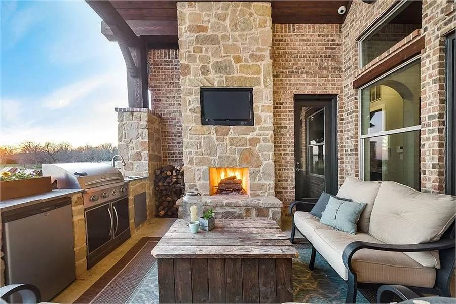 The outdoor living is filled with a stone fireplace, cushioned sofa, rustic table, and a summer kitchen.
