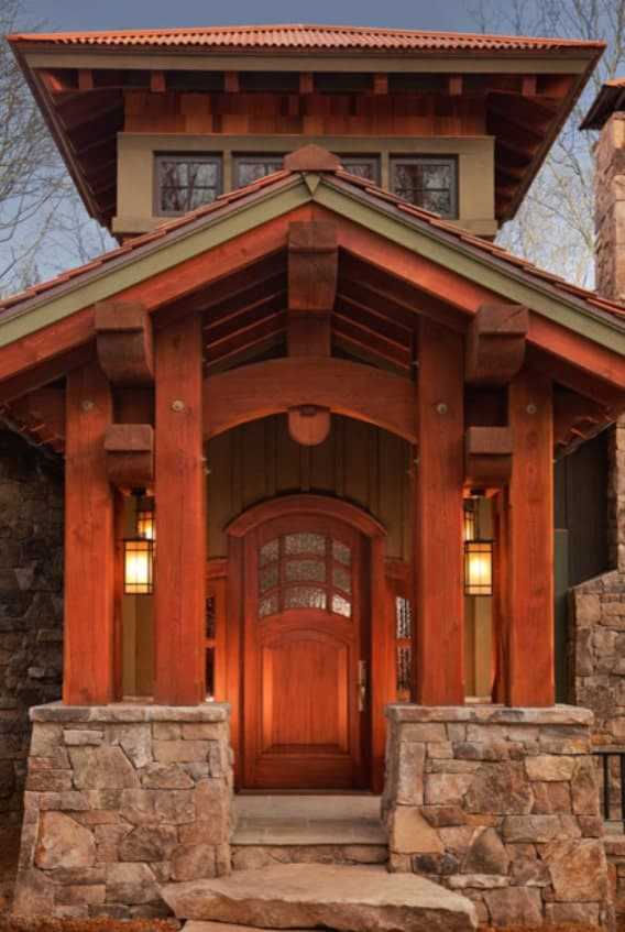 Home entry with double columns and an arched front door well-lit by warm glass sconces.