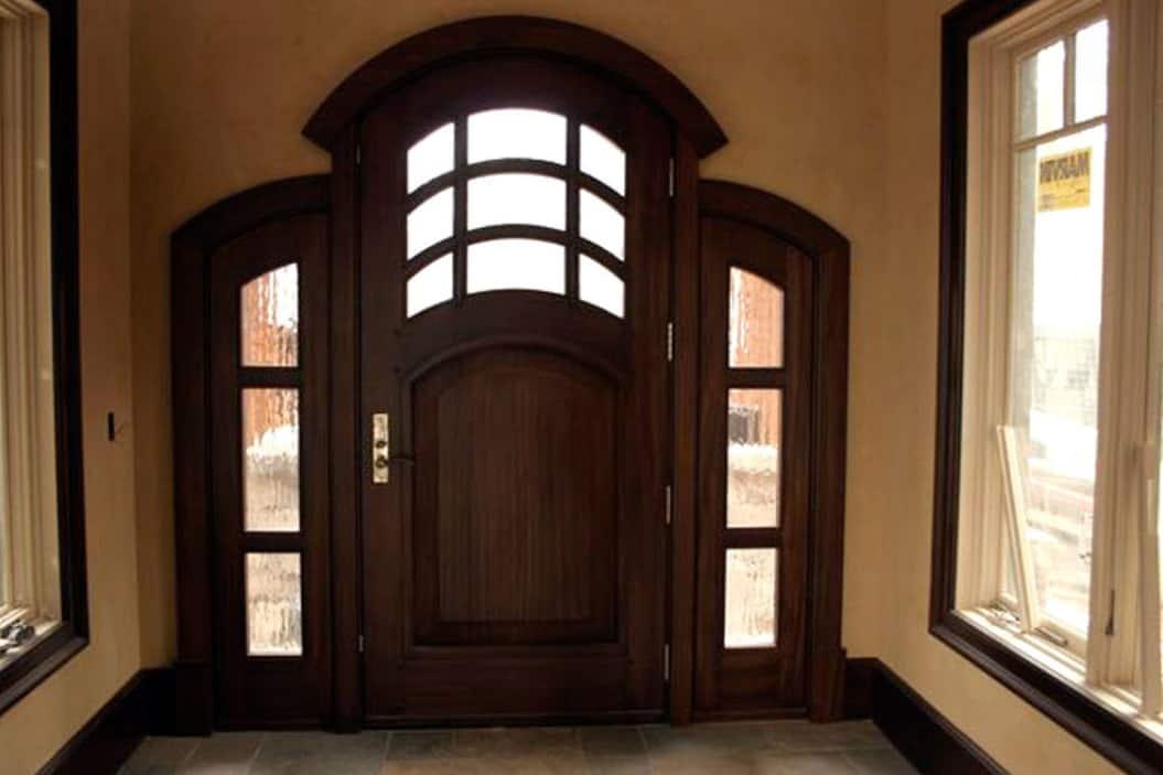 The foyer has framed windows and an arched front door fitted with glass panels.