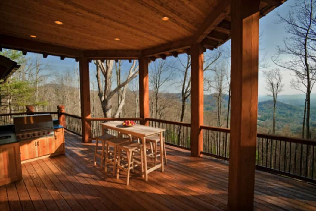 The covered deck is filled with a summer kitchen and an outdoor dining set.