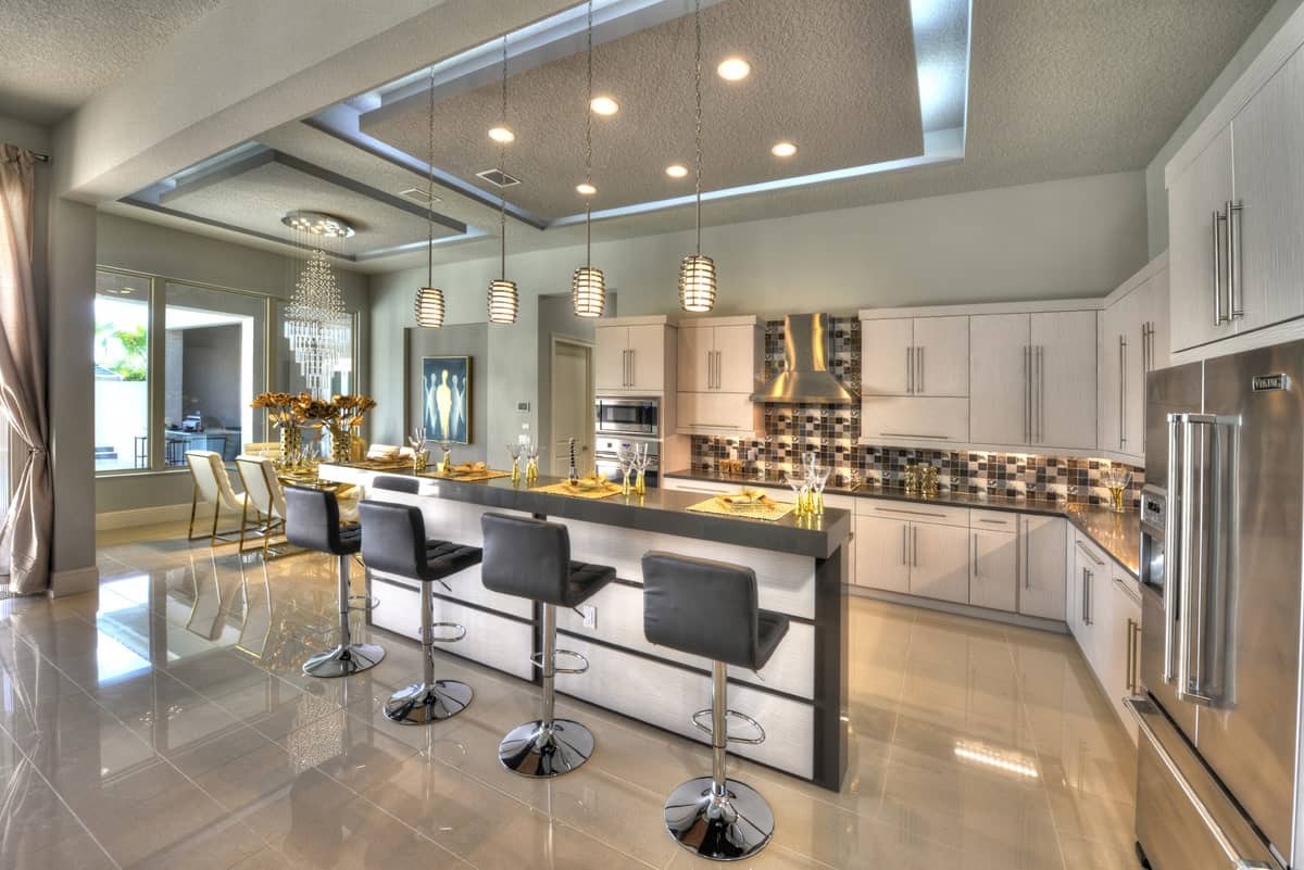 Eat-in kitchen with custom cabinetry, stainless steel appliances, mosaic tile backsplash, and a breakfast island.
