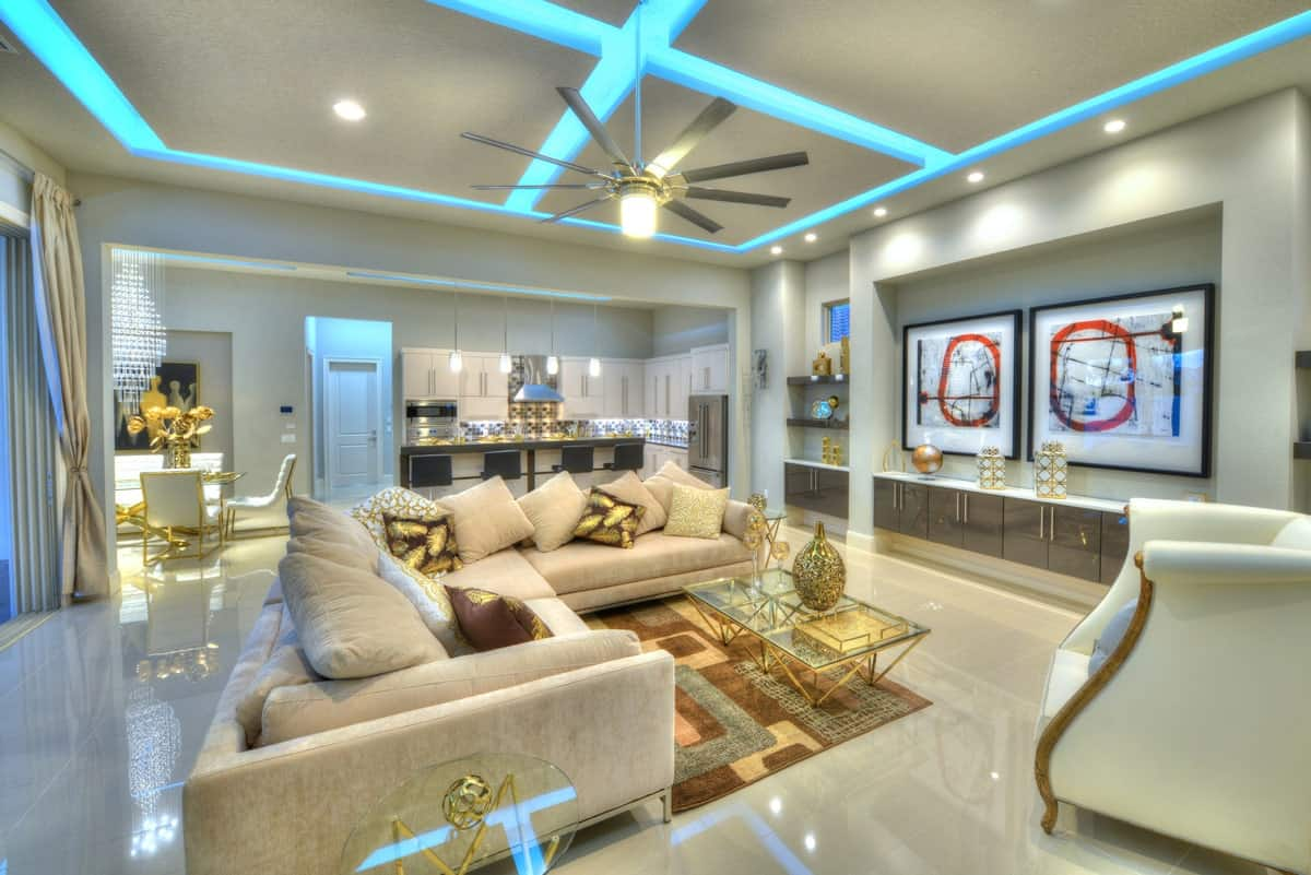 The living room has a beige sofa, glass top tables, classy white armchairs, and high gloss built-ins adorned with framed wall arts.