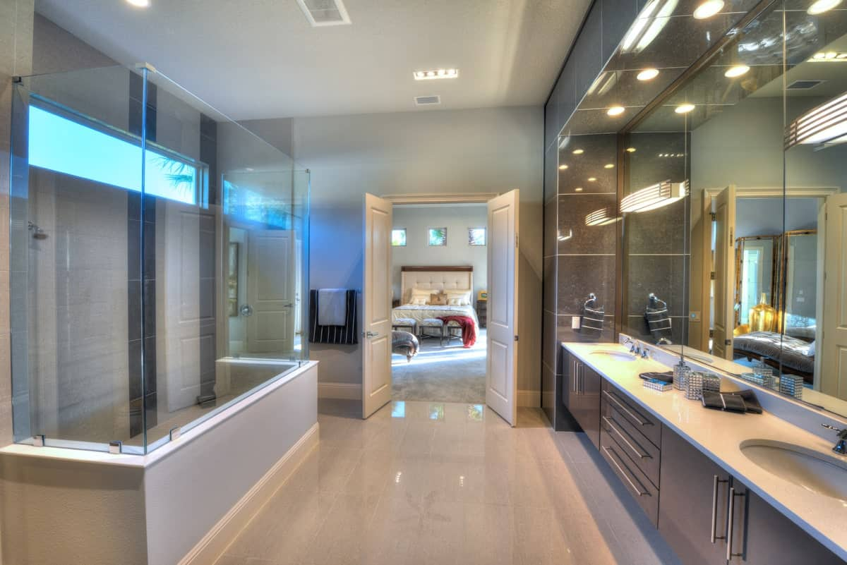 Primary bathroom with a spacious walk-in shower and a dual sink vanity paired with a large paneled mirror.