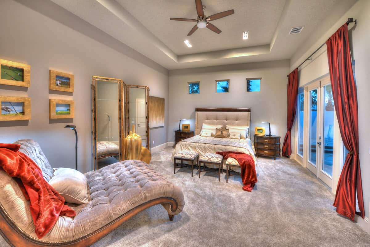 The primary bedroom has large vases, a tufted chaise lounge, and a cozy bed with cushioned footstools at its end.