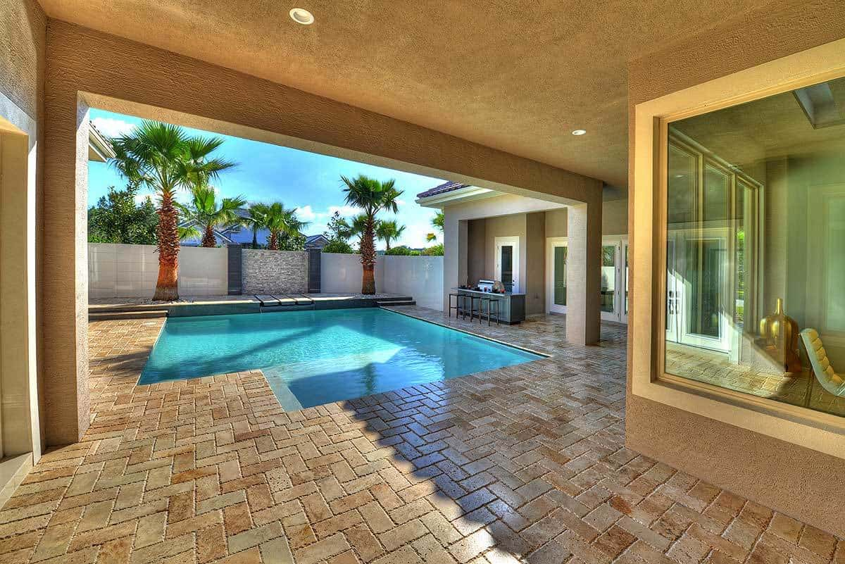 The outdoor living has stucco walls and brick flooring arranged in a herringbone pattern.