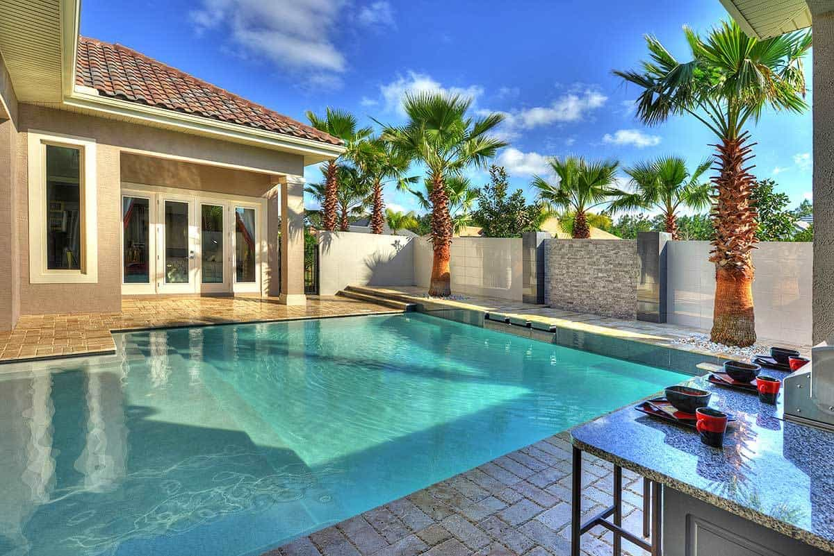 Towering palm trees and a stunning water feature grace the swimming pool.