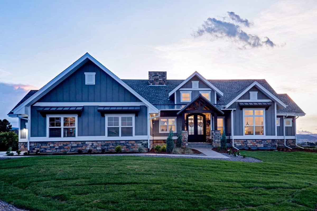 Front exterior view with gable rooflines, stone accents, and a covered porch lined with tapered columns.
