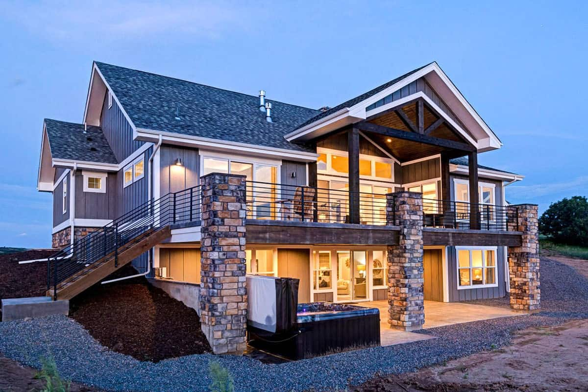Rear exterior view with covered patio and deck framed with rustic wood trims.