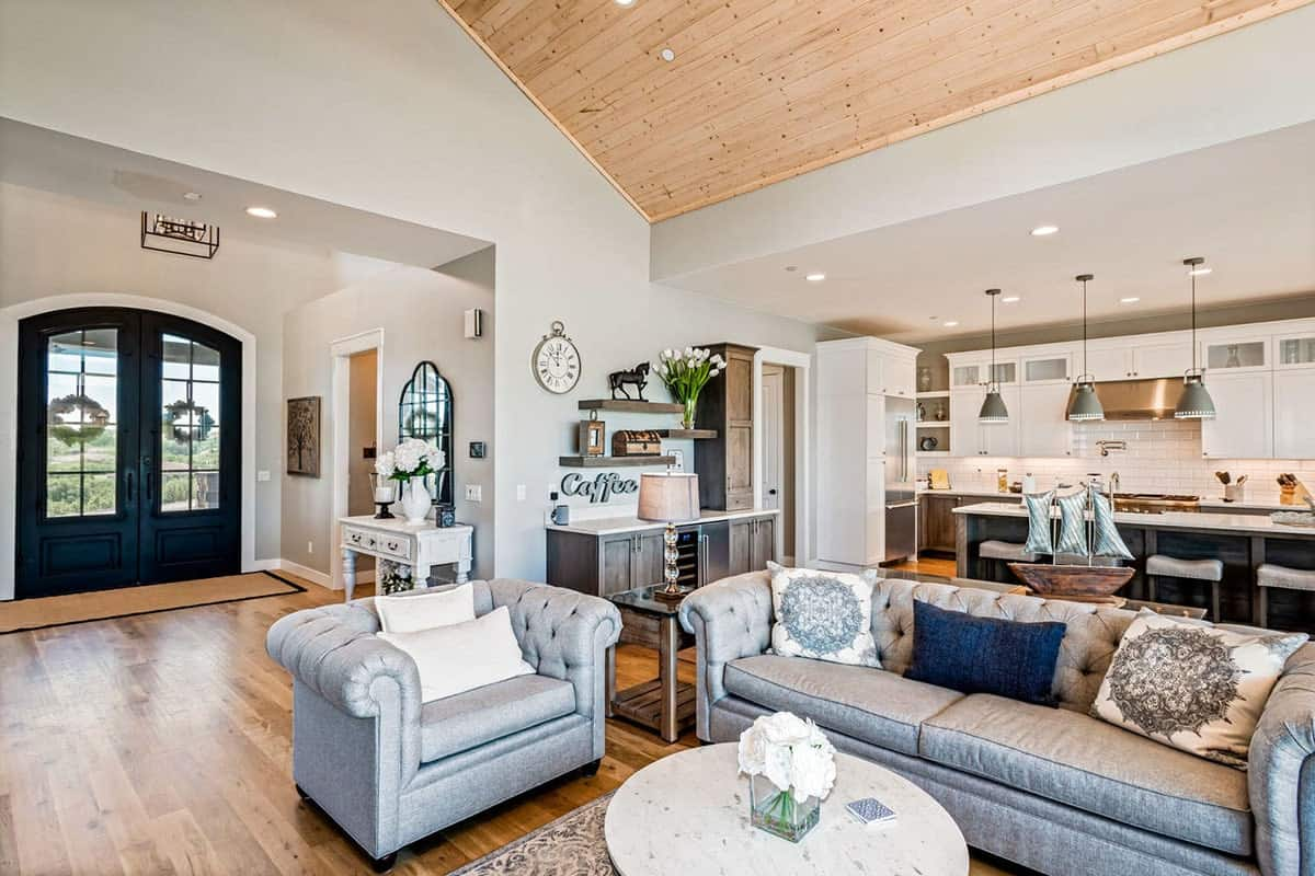 Living room with hardwood flooring and a cathedral ceiling clad in light wood planks.