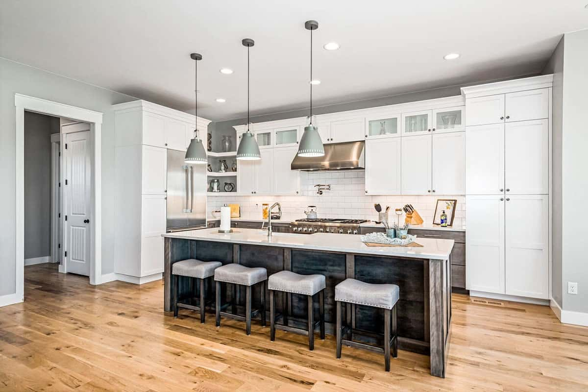 The kitchen is equipped with stainless steel appliances, white cabinetry, marble countertops, and a breakfast island.