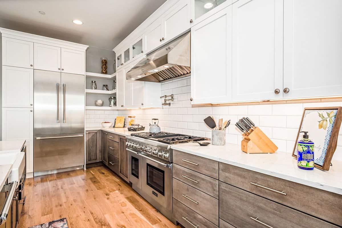 Subway tile backsplash adds texture to the white kitchen.