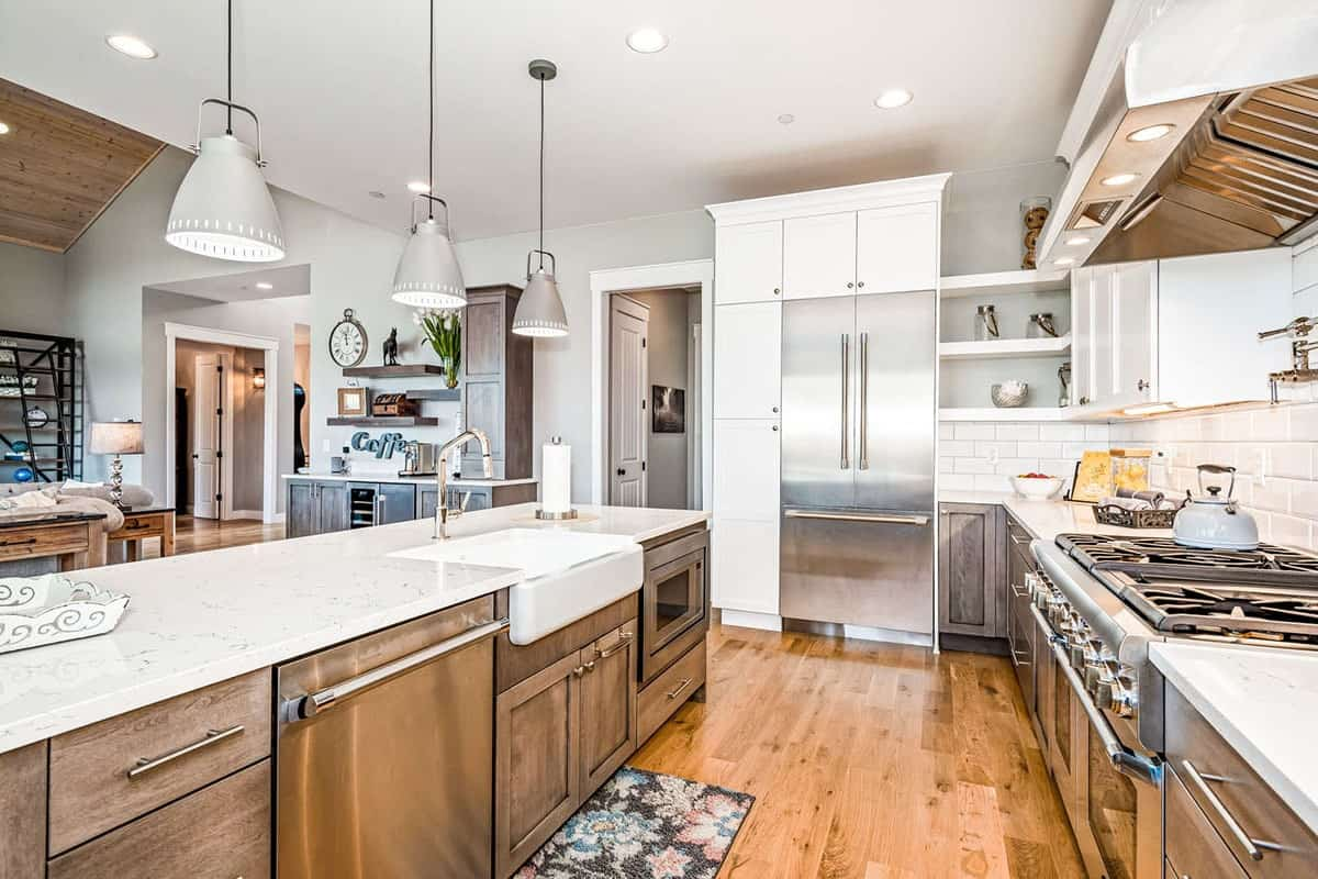 The kitchen island is fitted with a farmhouse sink, dishwasher, and an oven.