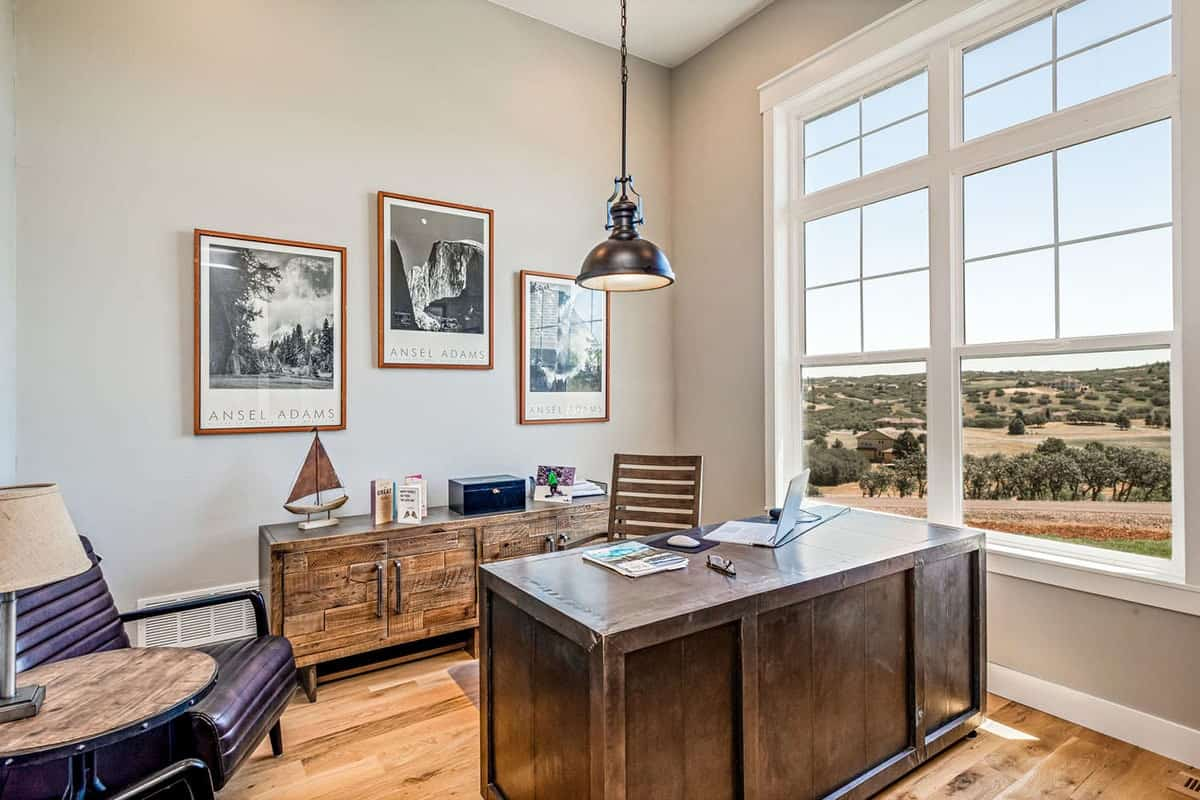 Study with a wooden desk, rustic cabinet, cozy chairs, and framed artworks adorning the light gray wall.