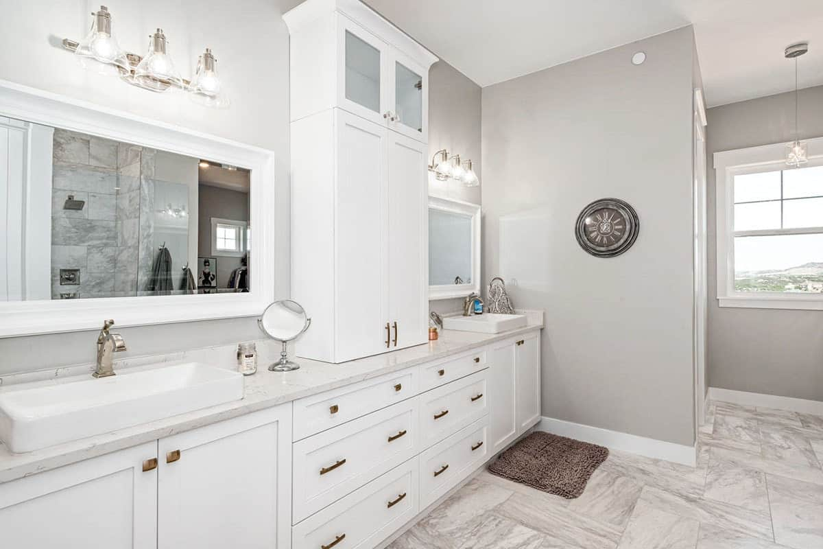 Primary bathroom with a toilet room, dual sink vanity, and a walk-in shower reflected in the white framed mirror.