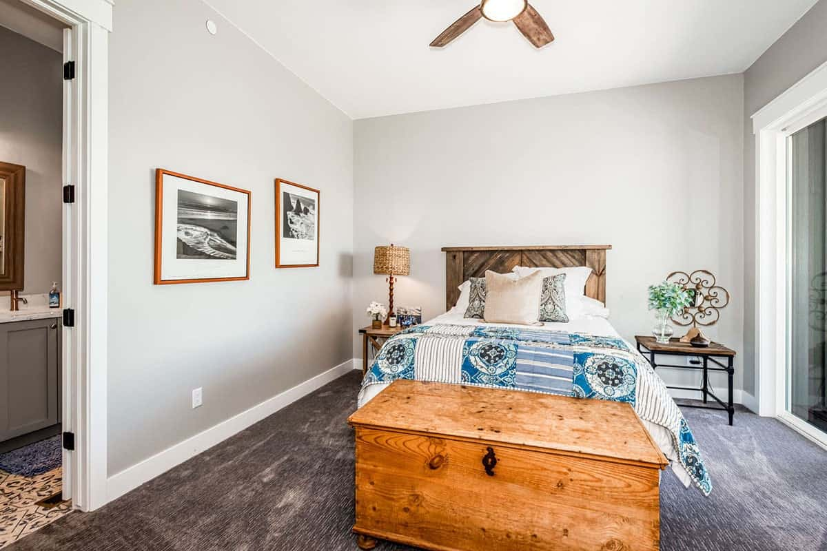 This bedroom has wooden furnishings, gray walls, carpet flooring, and a private bath.