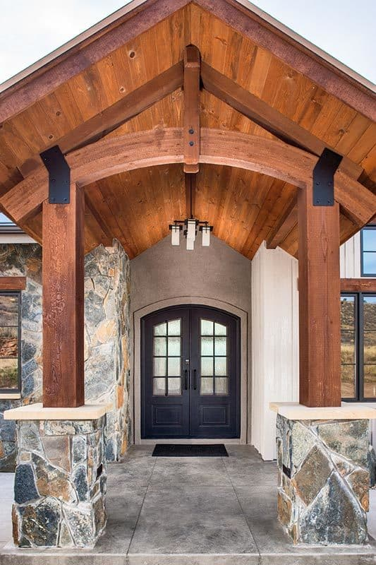 Covered entry with an arched front door, a cathedral ceiling, and tapered pillars.