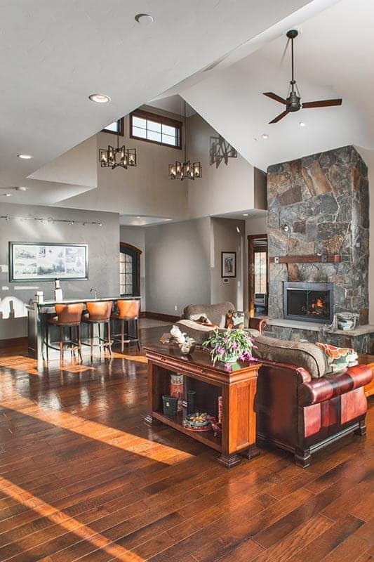 The living room has a stone fireplace, a wet bar, a leather sofa, and wooden tables that blend in with the hardwood flooring.
