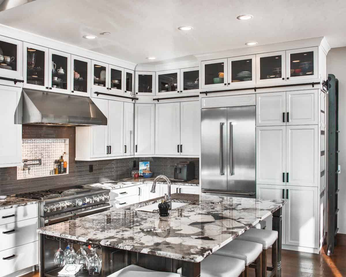 The kitchen is equipped with stainless steel appliances, granite countertops, white cabinets, and an immense island.