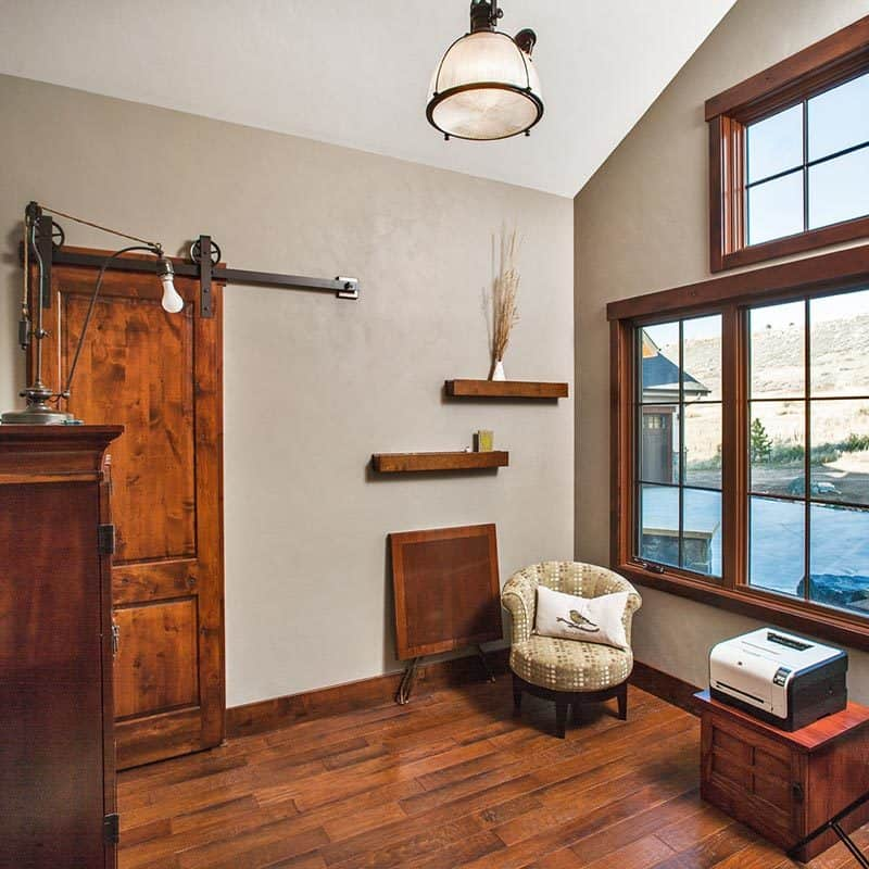 This room offers a wooden cabinet, round back chair, and wooden framed windows that invite natural light in.