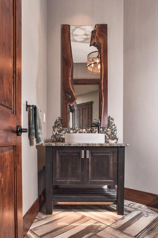 The powder room has a dark wood vanity with a vessel sink and a tall decorative mirror.