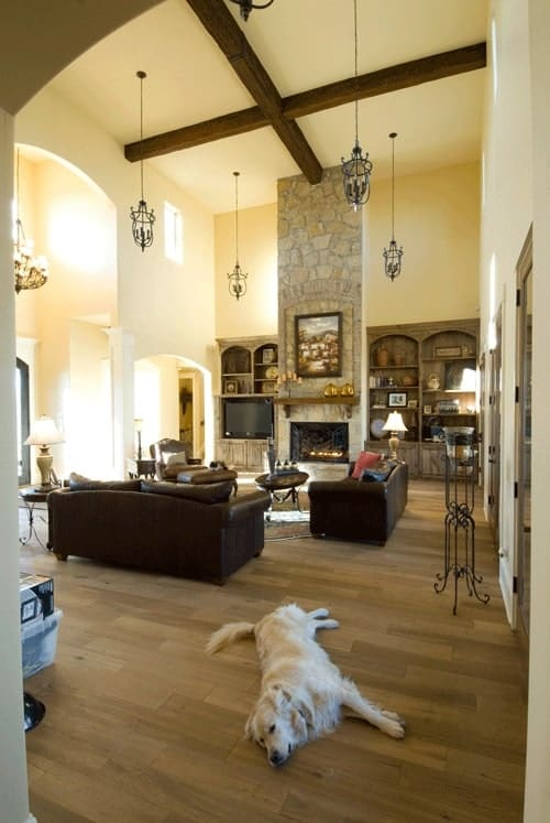 The living room has natural hardwood flooring, and a two-story ceiling mounted with wrought iron pendants.