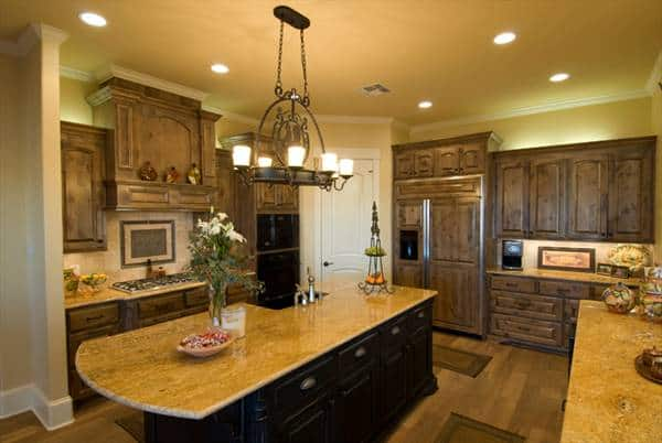 The kitchen is equipped with granite countertops, black appliances, wooden cabinetry, an ornate chandelier, and a large center island.