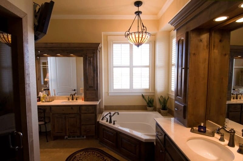 The primary bathroom offers a walk-in shower, separate his and her vanities, and a corner tub well-lit by a dome pendant.