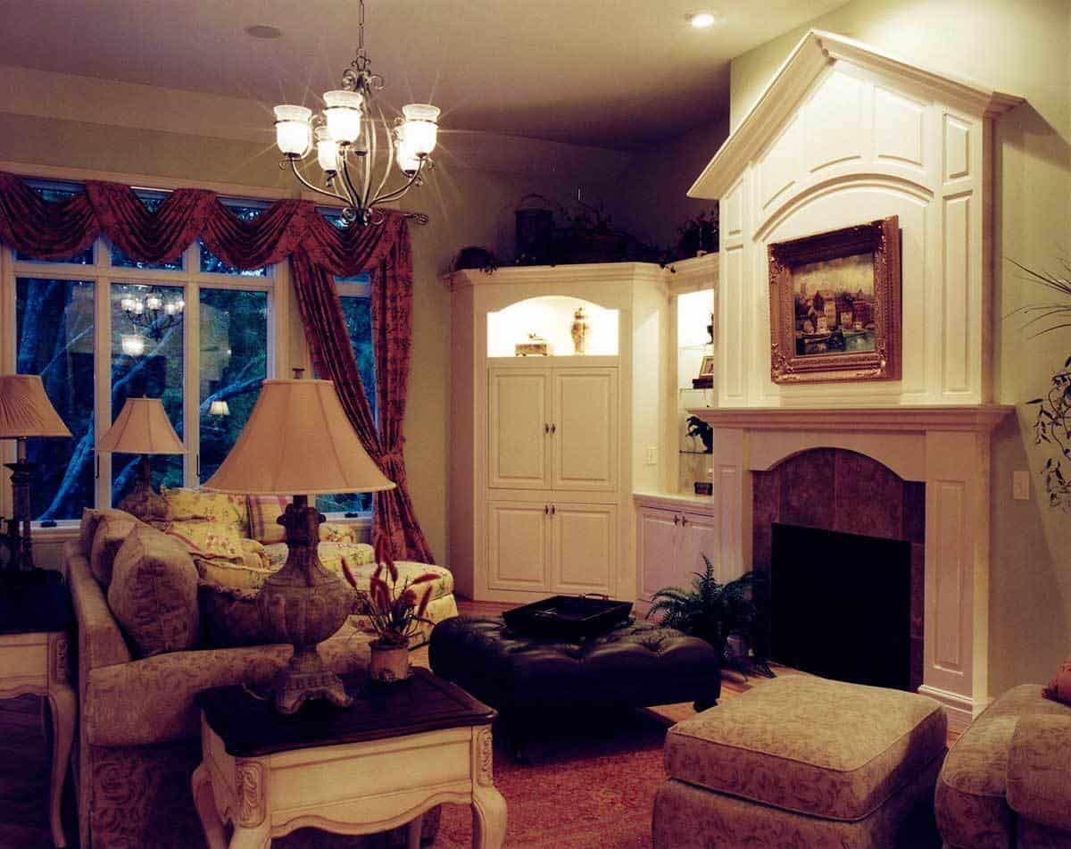 Living room with a fireplace, classy seats, wooden tables, white built-ins, and a tufted ottoman.