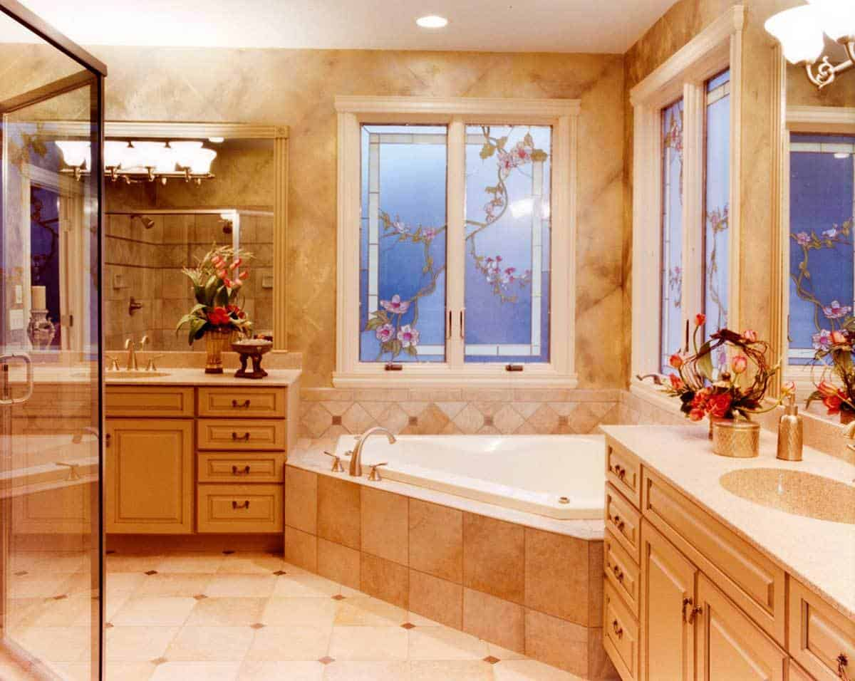 Primary bathroom with a walk-in shower, wooden vanities, and a corner bathtub placed under the glass stained windows.