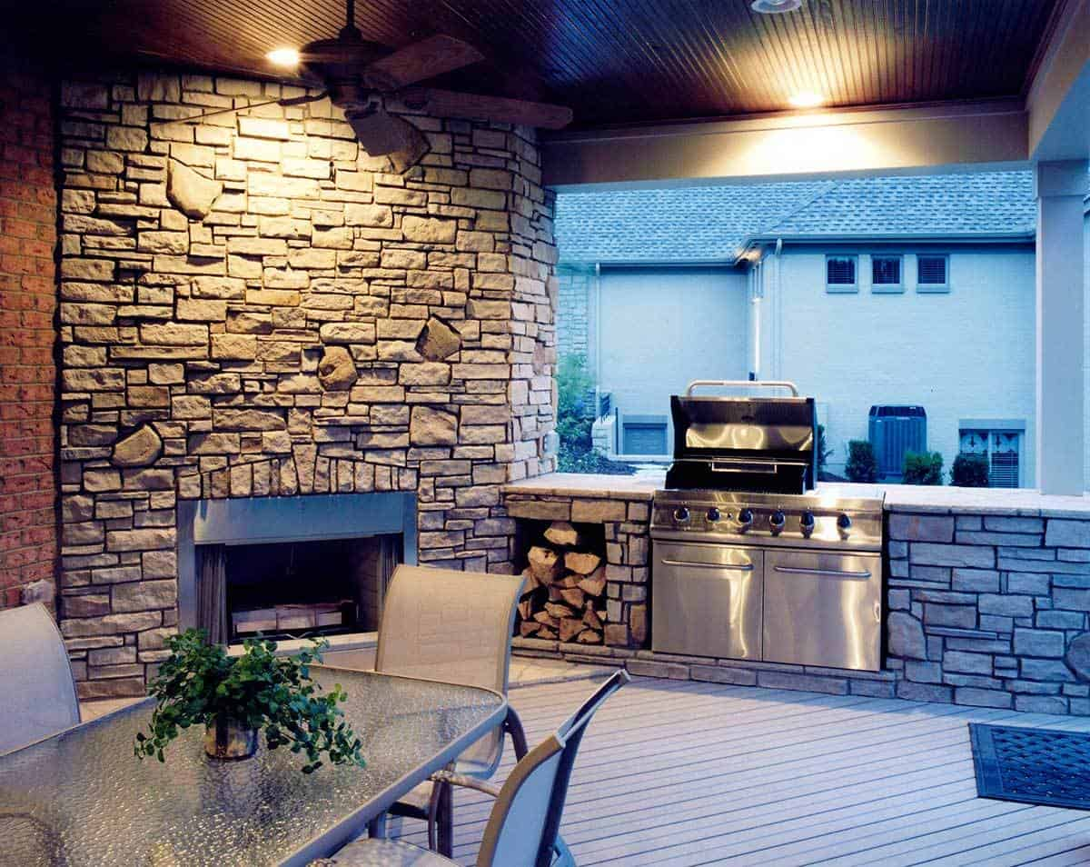 Covered deck with a summer kitchen, metal dining set, and a stone fireplace that matches the kitchen counter.