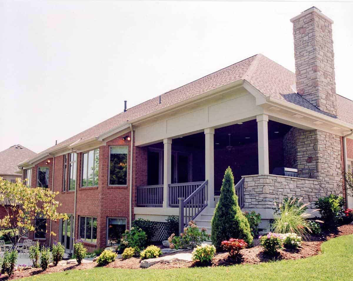 Rear exterior view showing the brick walls, stone chimney, white columns, and a covered deck with a stoop.