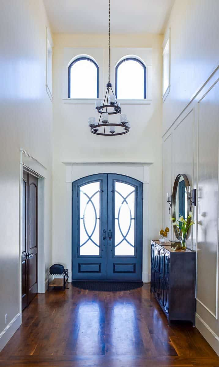 Foyer with a two-story ceiling, an arched entry door, and a dark wood console table paired with a round mirror.