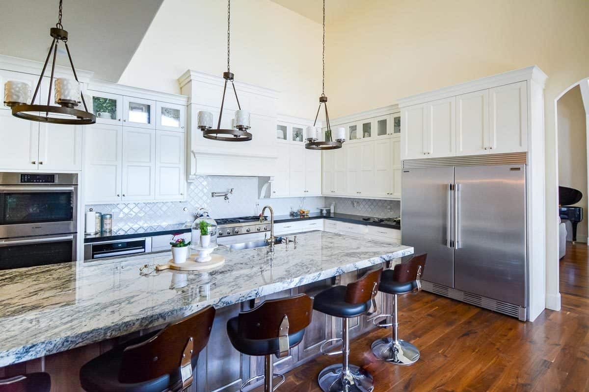 The kitchen is equipped with slate appliances, white cabinetry, granite countertops. round pendants, and a large center island.
