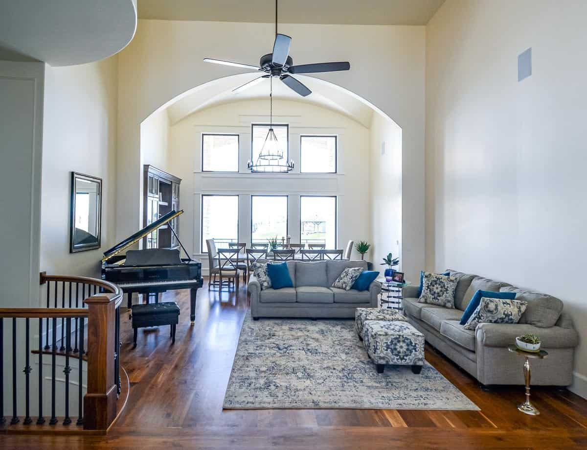 Family room with gray sectionals, baby grand piano, and patterned ottomans sitting on a distressed area rug.