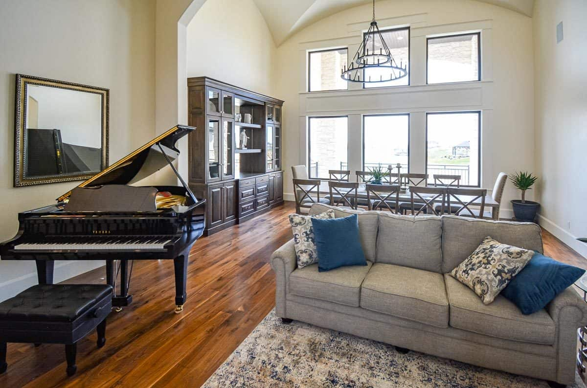 At the back of the family room is the dining area with a wooden display cabinet and a rectangular dining set well-lit by a two-tier chandelier.