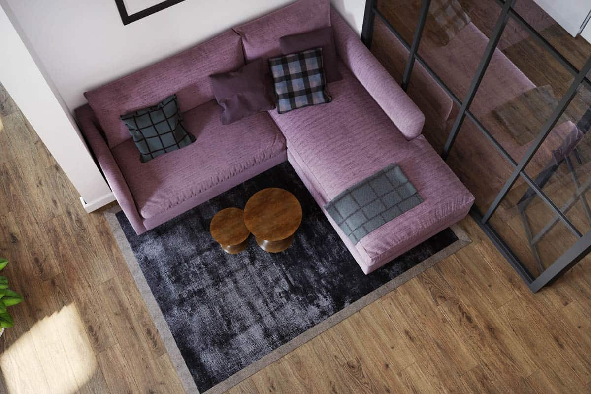 This is a top view of the living room area that has a large purple L-shaped sectional sofa paired with a couple of small wooden coffee table on a gray area rug that matches the pillows.